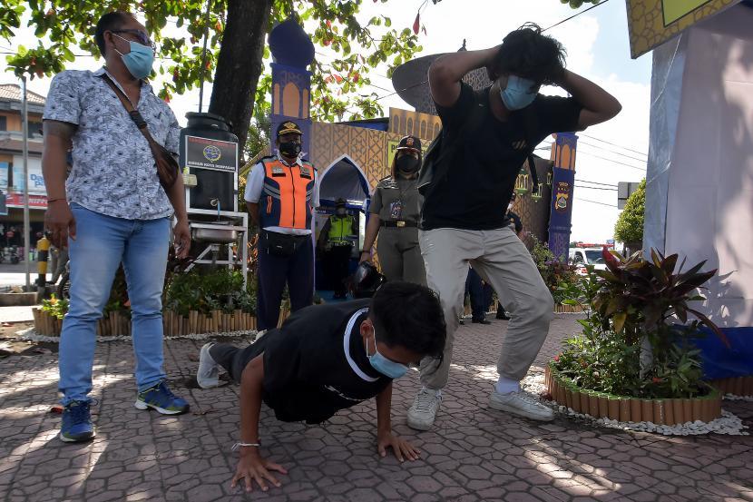 Petugas memberikan sanksi push up kepada pelanggar protokol kesehatan di Posko Uma Anyar, Kota Denpasar, Bali, Senin (10/5/2021).