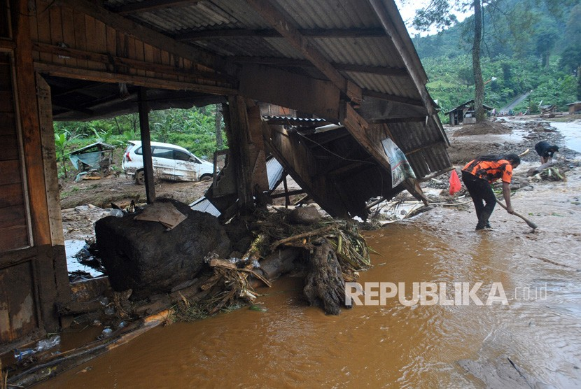 Petugas membersihkan material lumpur akibat banjir bandang yang menutupi ruas jalan Sukamakmur-Cianjur di Kampung Cisarua RT 04/05, Desa Sukawangi, Sukamakmur, Kabupaten Bogor, Jawa Barat, Ahad (8/4).