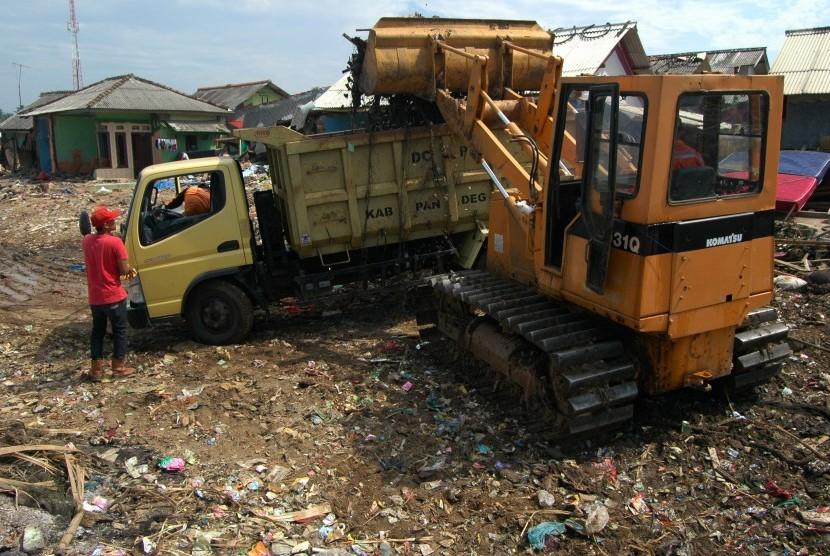Petugas membersihkan puing-puing rumah dan sampah pasca terjangan tsunami Selat Sunda di Kampung Teluk Nelayan I, Labuan, Pandeglang, Banten, Rabu (9/1/2019).