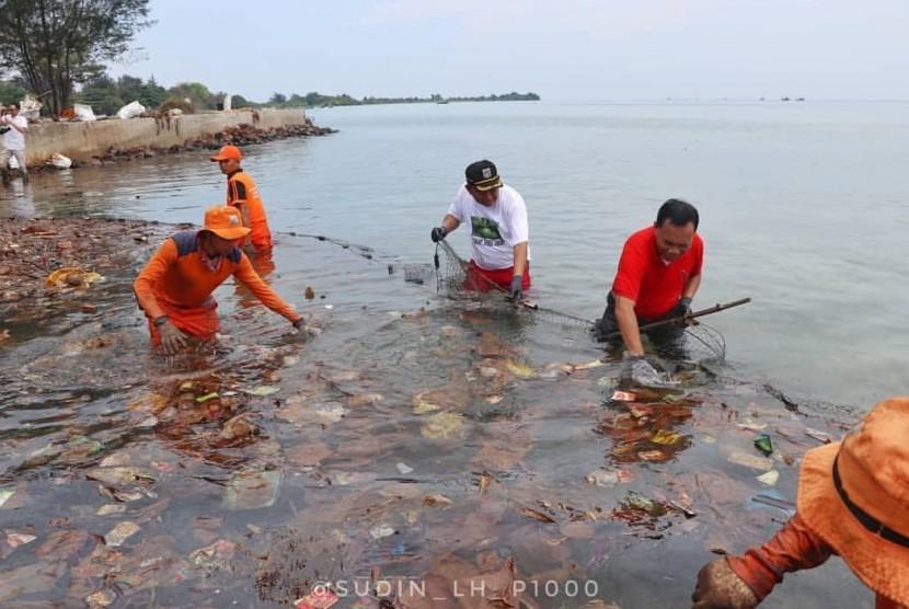 Petugas membersihkan sampah di Pulau Pari, Kepulauan Seribu, Kamis (29/11).