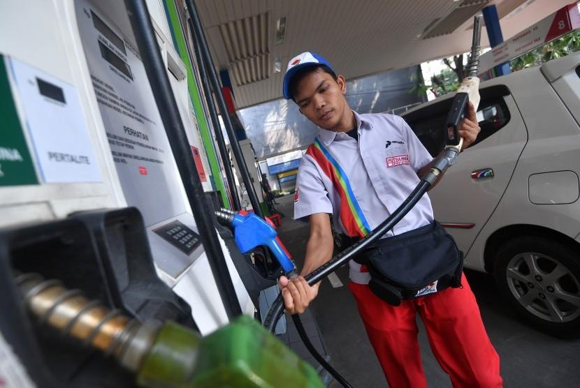 Petugas memegang nozel seusai mengisi bensin kendaraan konsumen.