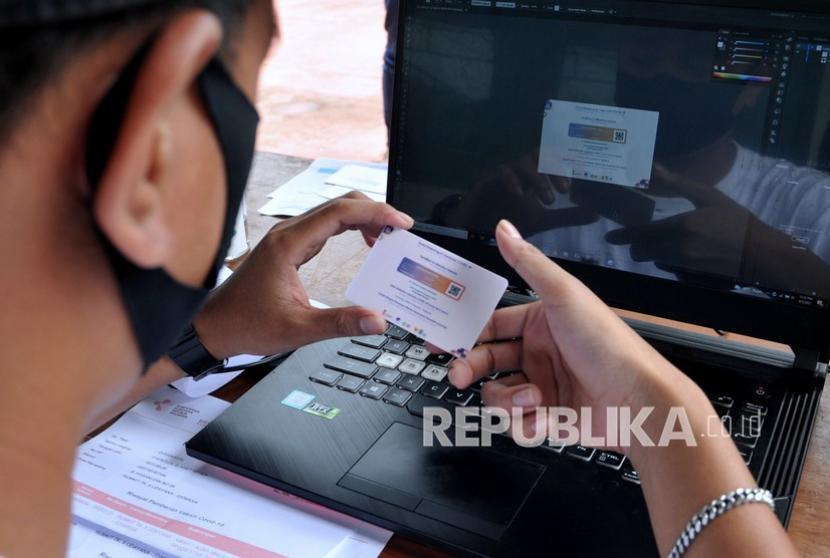 Petugas memeriksa cetakan kartu sertifikat vaksinasi COVID-19 pesanan warga saat kegiatan vaksinasi COVID-19 massal di Denpasar, Bali, Selasa (3/8/2021). Jasa cetak Surat Keterangan Vaksinasi COVID-19 tersebut dijual dengan harga Rp25 ribu per buah.