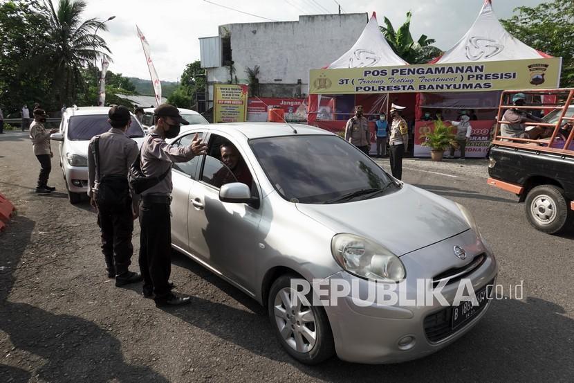 Petugas memeriksa identitas pengendara saat melakukan penyekatan pemudik di Ajibarang, Banyumas.