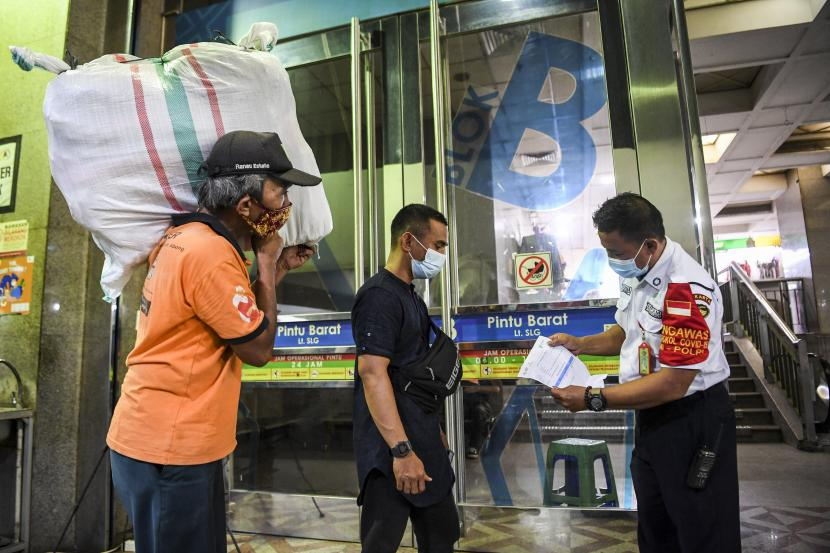 Petugas memeriksa kartu vaksinasi seorang pedagang yang akan memasuki Blok B Pasar Tanah Abang, Jakarta, Senin (26/7/2021). Pasar Tanah Abang kembali dibuka mulai Senin (26/7), mengikuti penyesuaian aturan Pemberlakuan Pembatasan Kegiatan Masyarakat (PPKM) level 4 yang telah ditetapkan pemerintah dengan syarat seluruh pedagang, pegawai toko dan pengunjung yang akan masuk sudah divaksin COVID-19 dan dibuktikan dengan menunjukkan kartu vaksinasi