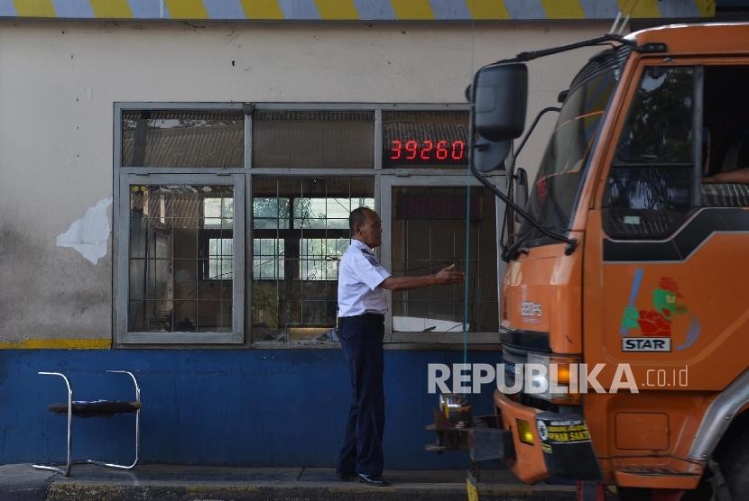 Petugas memeriksa surat-surat kendaraan di jembatan timbang Losarang, Indramayu, Jawa Barat, Senin (20/6). (Republika/Raisan Al Farisi)