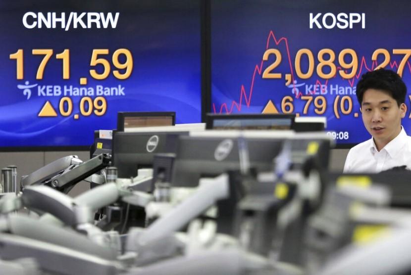 Petugas memperhatikan monitor yang menunjukkan pergerakan saham di KEB Hana Bank di Seoul, Korea Selatan, Selasa (16/7). Bank Sentral Korea Selatan secara tiba-tiba memangkas suku bunga acuan pada Kamis (18/7).