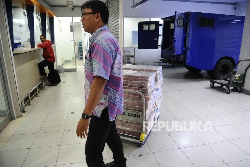 Petugas menarik troley berisi uang di Polling Cash Bank Mandiri, Jakarta, Kamis (9\2)