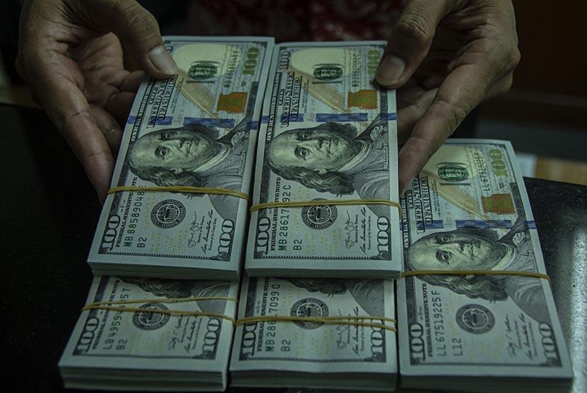 Petugas menata pecahan dolar Amerika di salah satu gerai penukaran mata uang di Kwitang, Jakarta, Jumat (18/5). Nilai tukar rupiah di pasar spot yang ditransaksikan pada Jumat (18/5) ditutup melemah 98 poin atau terdepresiasi 0,70 persen ke level Rp14.156 per dolar AS.