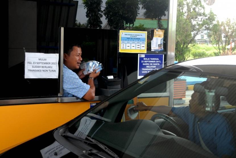 Petugas menawarkan e-money di gerbang pintu tol Jagorawi Citeureup, Kabupaten Bogor, Jawa Barat, Senin (16/10).