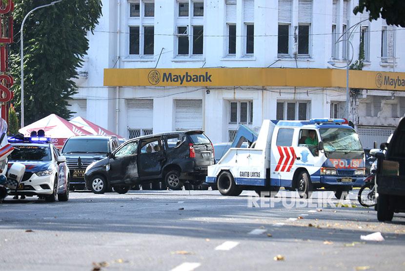 Petugas menderek mobil terdampak ledakan di Polrestabes Surabaya, Jawa Timur, Senin (14/5).