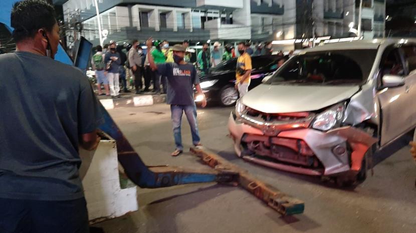 Petugas menderek mobil Toyota Calya yang menabrak dua kendaraan lainnya di Jalan Arif Rahman Hakim, dekat Tugu Tani, Menteng, Jakarta Pusat, Jumat (5/2) pukul 18.00 WIB.