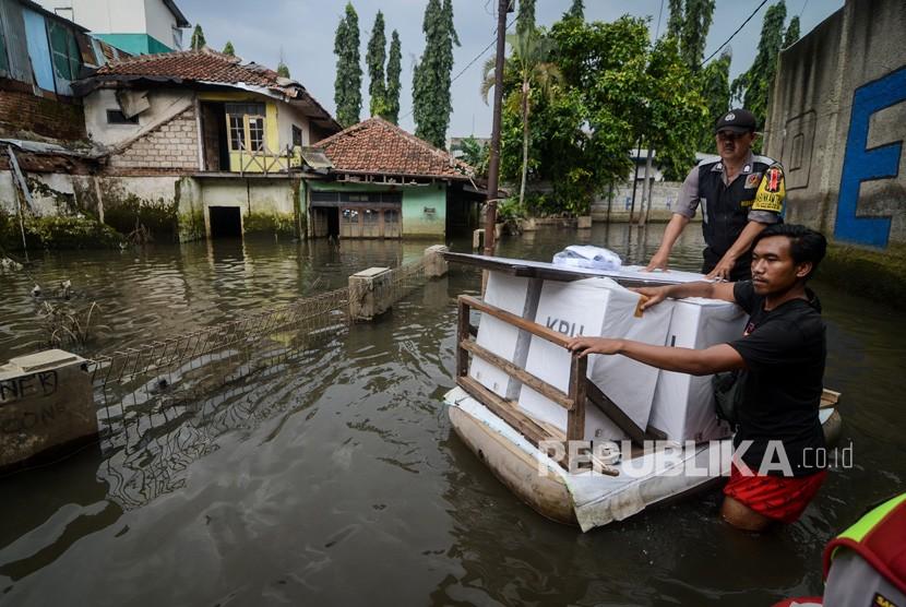 Petugas menerjang banjir dengan menggunakan perahu saat mendistribusikan logistik keperluan Pemilu dan Pileg di Desa Bojongasih, Dayeuhkolot, Kabupaten Bandung, Jawa Barat, Selasa (16/4/2019).