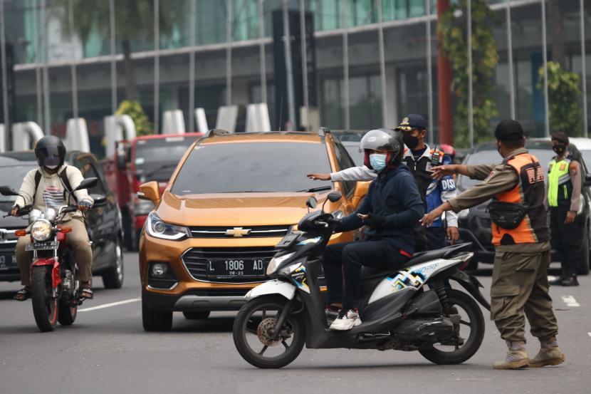Petugas mengalihkan pengendara motor yang akan masuk ke Surabaya saat penyekatan PPKM Darurat, di Bundaran Waru, Surabaya, Jawa Timur.