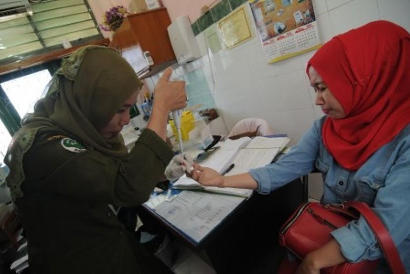 Petugas mengambil sampel darah salah seorang calon jamaah haji di Puskesmas Kamonji Palu, Sulawesi Tengah, Senin (3/8).