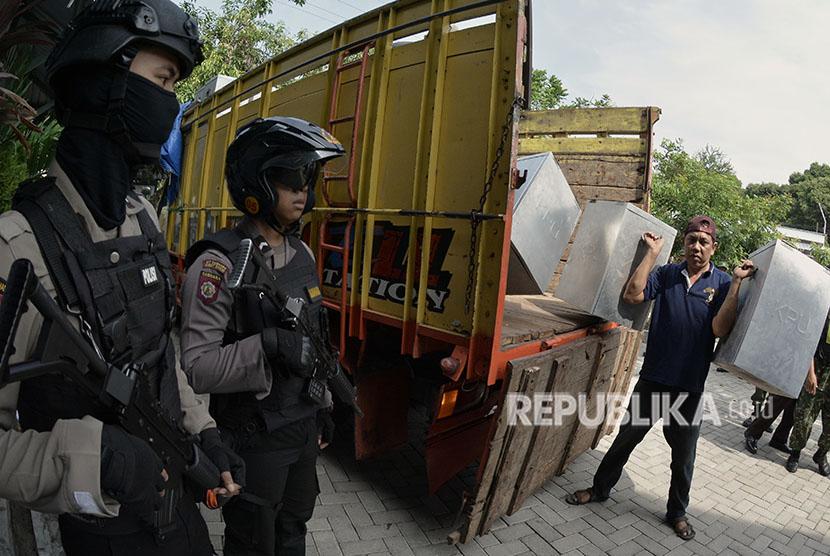 Petugas mengangkat kotak suara berisi logistik Pilkada Kota Madiun dan Pilgub Jatim yang didistribusikan di kawasan Nambangan Kidul, Madiun, Jawa Timur, Senin (25/6).