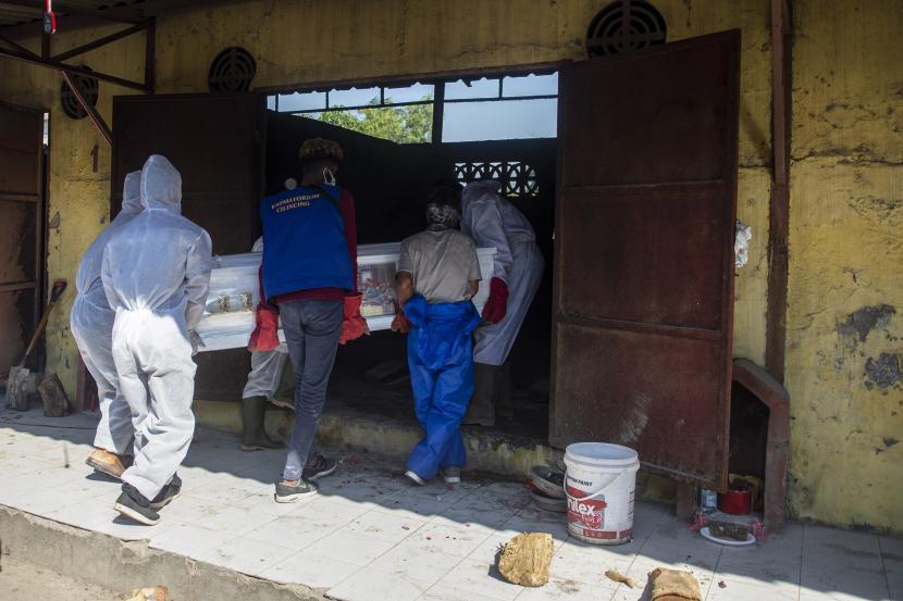 Petugas mengangkat peti jenazah untuk kremasi dengan pemulasaraan Covid-19 di Krematorium Cilincing, Jakarta Utara, Ahad (25/7). Pada Selasa (27/7), angka kematian harian Covid-19 di Indonesia mencetak rekor tertinggi sebanyak 2.096 kasus. (ilustrasi)