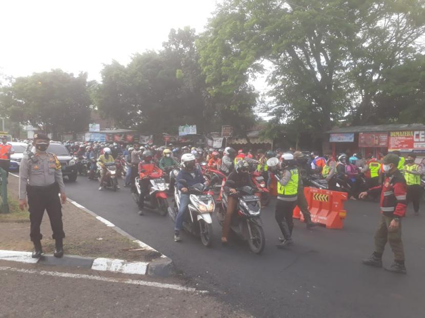 Petugas mengecek kelengkapan surat-surat kepada pengendara roda dua dan empat di posko penyekatan di Cibiru perbatasan Kota Bandung-Kabupaten Bandung di masa PPKM Darurat, Kamis (15/7).