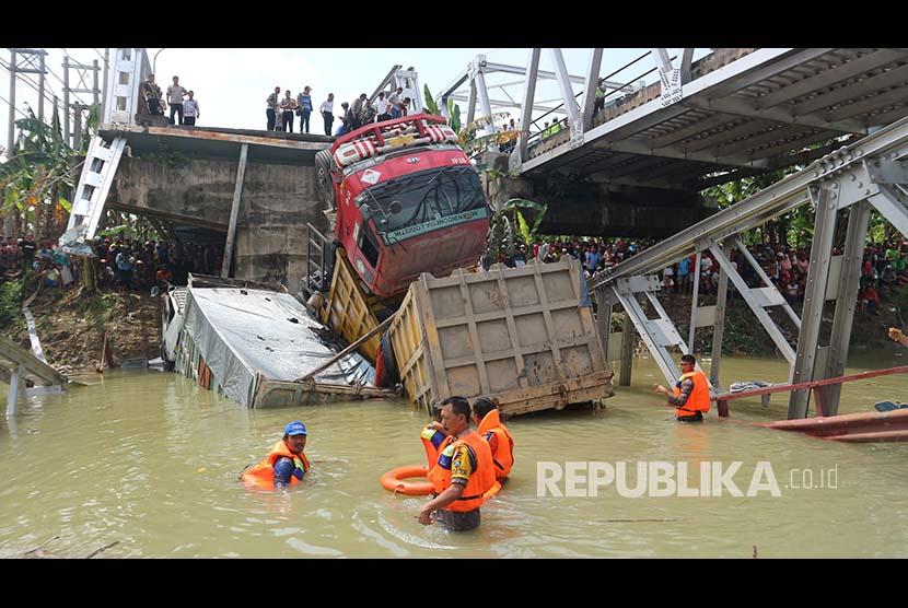 Petugas mengevakuasi truk di lokasi jembatan Widang yang runtuh, Tuban, Jawa Timur, Selasa (17/4). Sisi barat jembatan itu runtuh sekitar 50 meter dan mengakibatkan satu pengemudi truk meninggal dunia, dan melukai tiga korban lainnya, sementara tiga truk dan sebuah sepeda motor masuk ke Bengawan Solo.