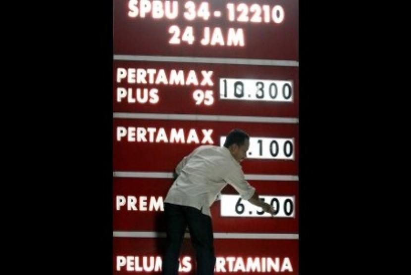 Petugas mengganti papan angka harga Bahan Bakar Minyak (BBM) di SPBU