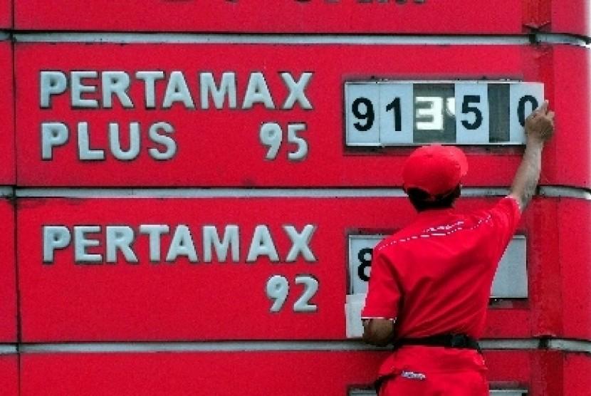 Petugas mengganti papan penunjuk harga bahan bakar di salah satu SPBU di Jakarta.