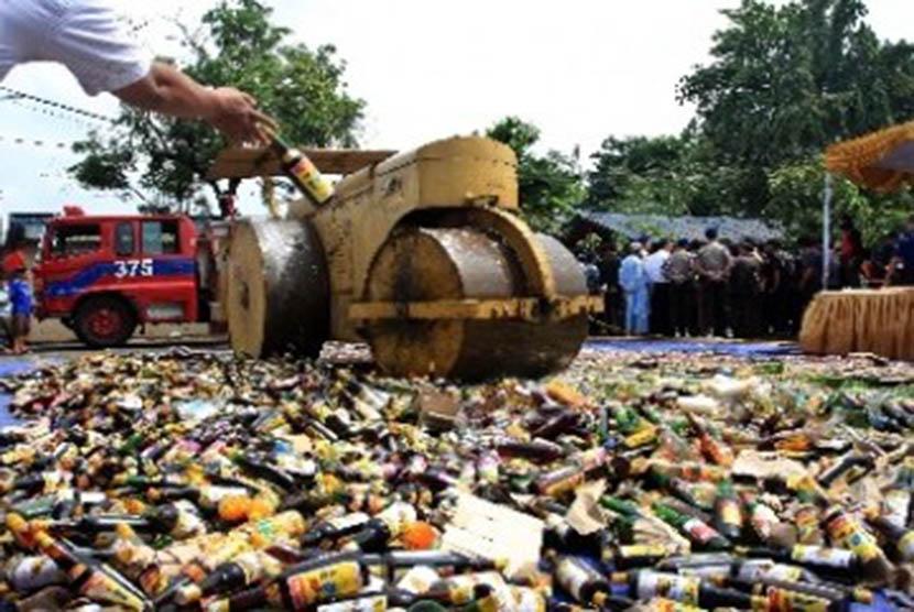 Petugas menggunakan alat berat memusnahkan ribuan botol minuman keras (miras).