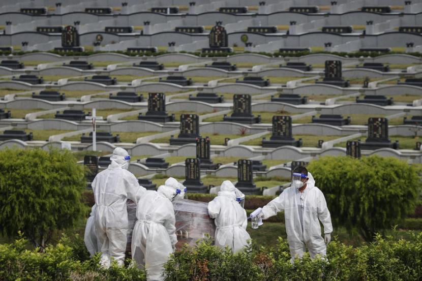 Petugas menggunakan APD menggotong peti mati jenazah Covid-19 di tempat pemakaman (ilustrasi).