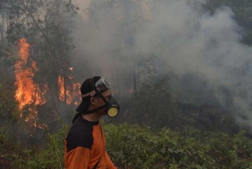 Petugas menggunakan masker ketika berusaha memadamkan api yang muncul di lahan gambut di sekitar Pulang Pisau, Kalteng, Selasa (27/10).