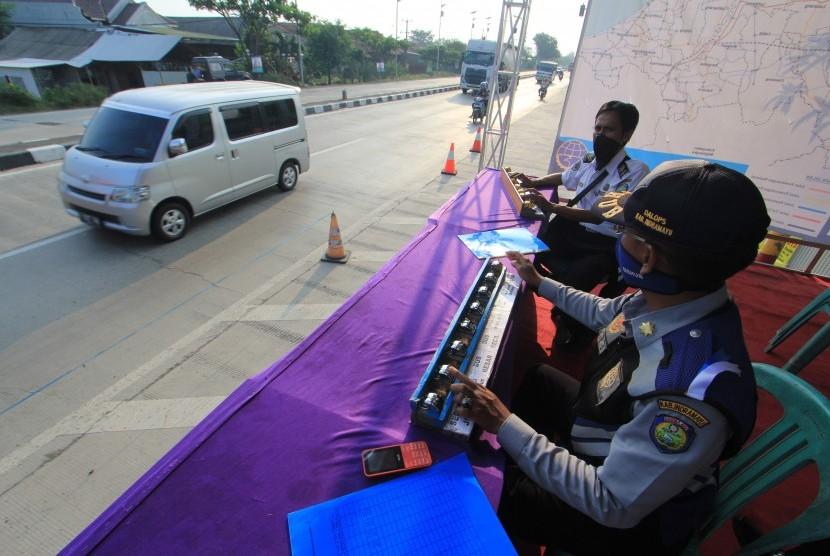 Petugas menghitung kendaraan yang melintas di Jembatan Timbang, Losarang, Indramayu, Jawa Barat, Jumat (8/6).