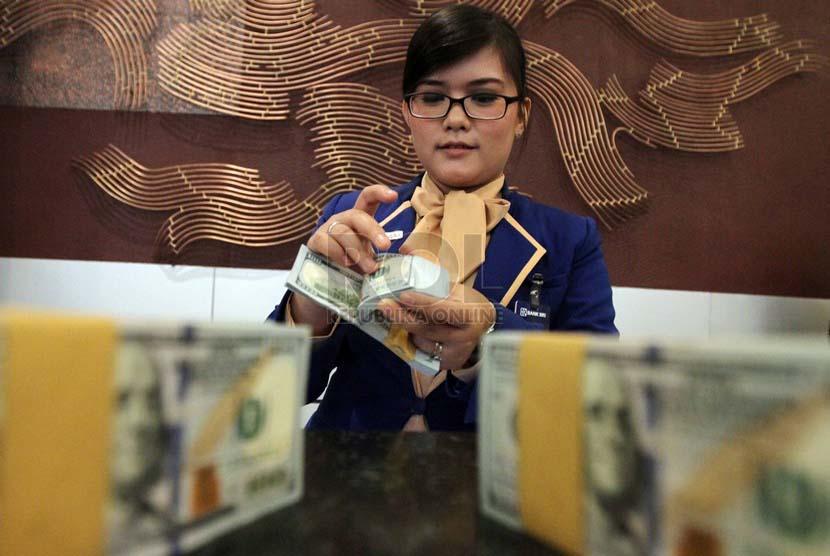 Petugas menghitung mata uang dollar Amerika, di Kantor Bank BRI, Jakarta, Kamis (3/7).(Republika/Adhi Wicaksono).