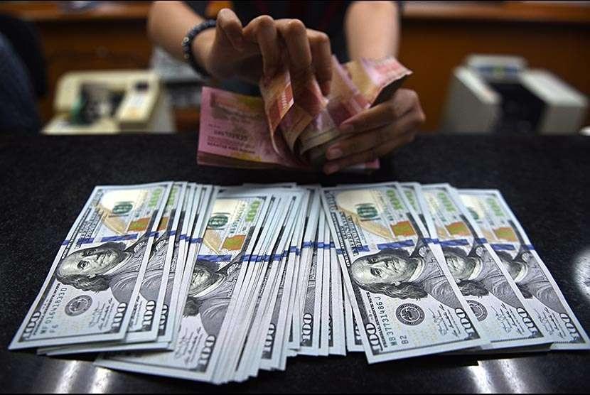 Petugas menghitung mata uang rupiah dan dolar AS di salah satu tempat penukaran uang di Jakarta, Selasa (9/10).