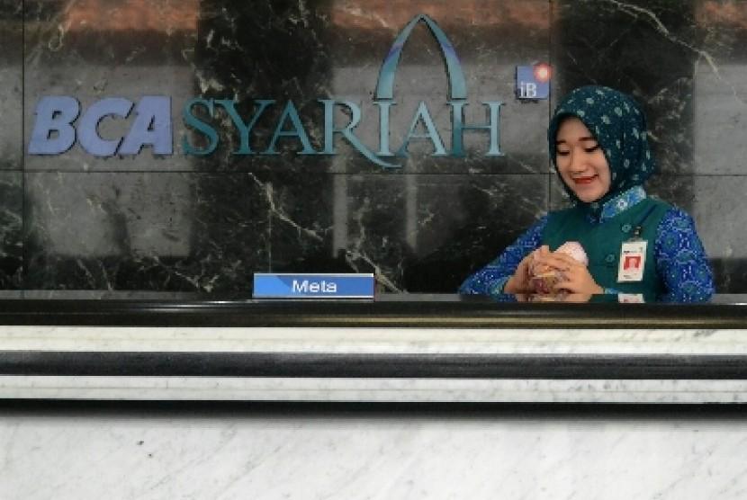 Petugas menghitung uang nasabah di kantor cabang Bank BCA Syariah, Jakarta.