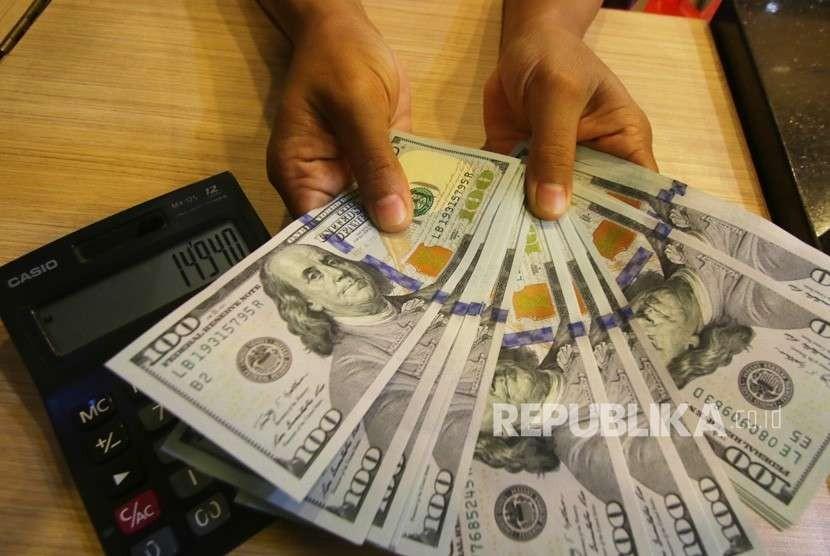 Petugas menghitung uang pecahan dolar Amerika Serikat di gerai penukaran mata uang asing di Jakarta, Selasa (4/9).
