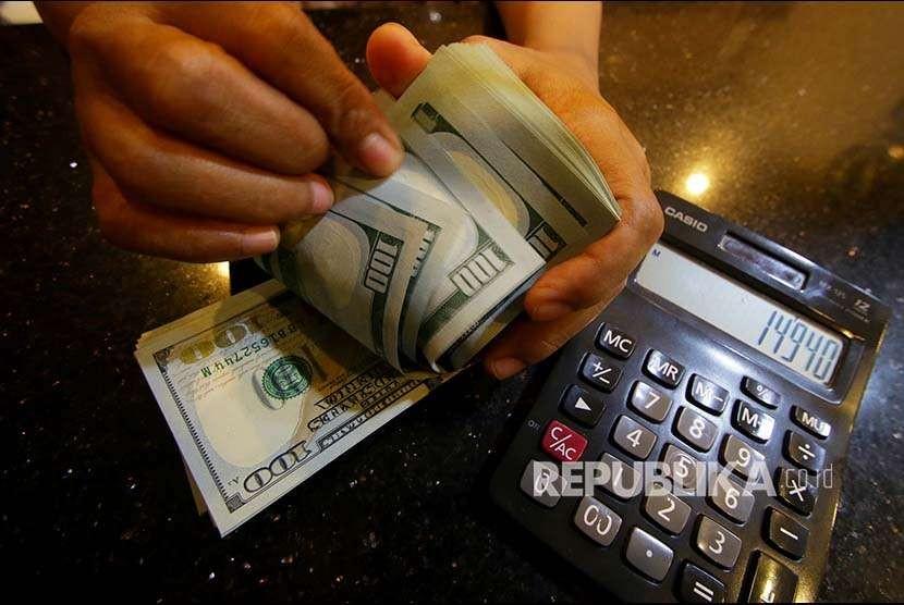 Petugas menghitung uang pecahan dolar Amerika Serikat di gerai penukaran mata uang asing di Jakarta, Selasa (4/9). Nilai tukar Rupiah terhadap Dollar AS melemah menjadi Rp14.940 per dolar AS pada perdagangan hari ini.