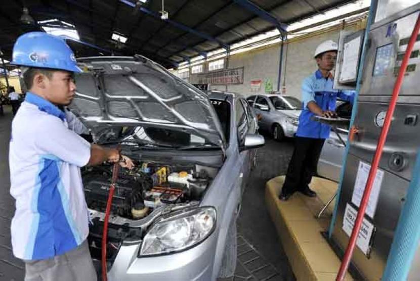 Petugas mengisi bahan bakar gas ke sebuah mobil di Stasiun Pengisian BBG (SPBG), Surabaya, Jawa Timur.