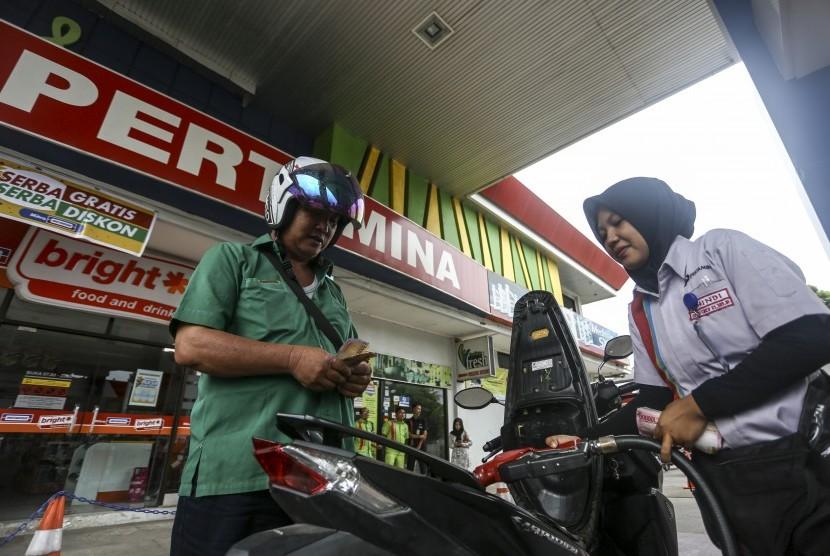 Petugas mengisi Bahan Bakar Minyak (BBM) kedalam tangki kendaraan roda dua di Stasiun Pengisian Bahan Bakar Umum (SPBU) Koko Kenten Palembang, Sumatera Selatan, Sabtu (5/1/2019).