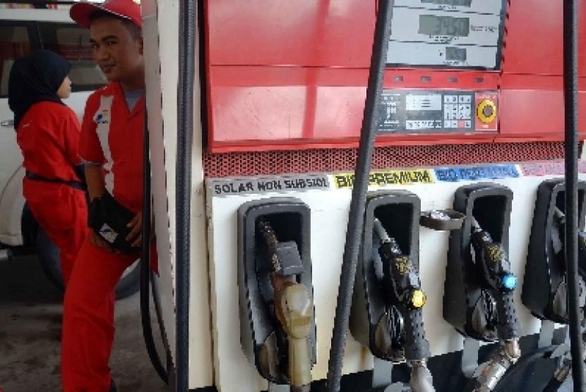 Petugas mengisi BBM ke sejumlah kendaraan di salah satu SPBU di Jakarta, Ahad (1/2).