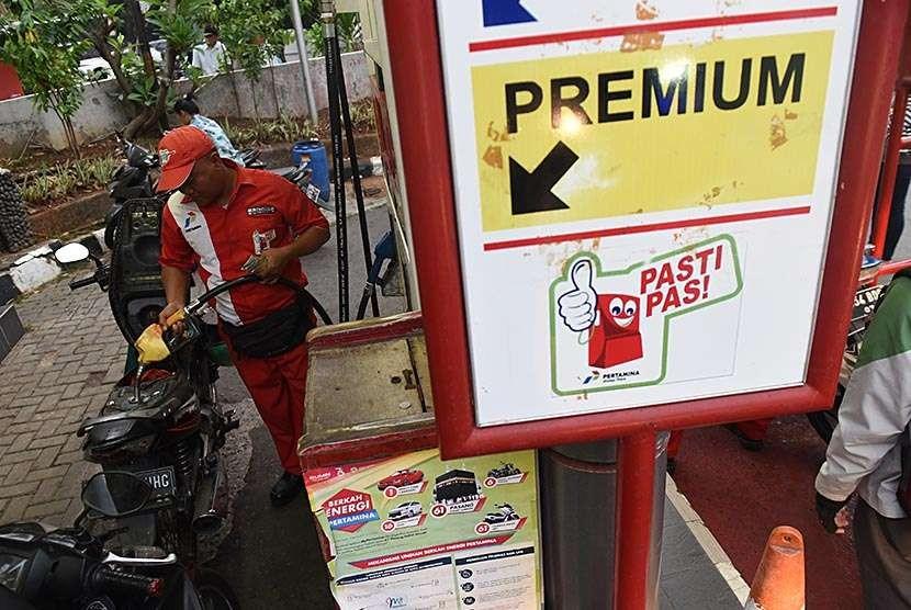 Petugas mengisi premium ke dalam sepeda motor di salah satu SPBU di Jakarta, Rabu (10/10). Pemerintah memutuskan untuk menunda rencana kenaikan BBM jenis premium sembari menunggu kesiapan dari Pertamina untuk menjalankan kebijakan tersebut.