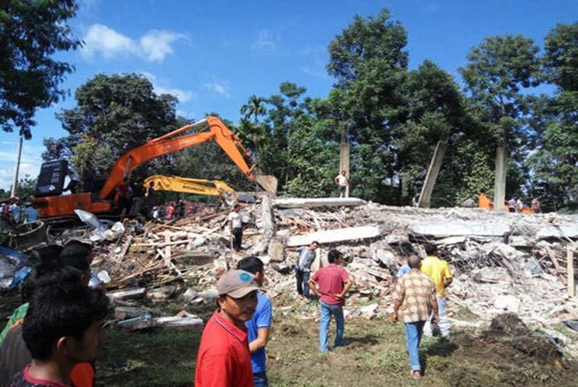 Petugas mengoperasikan alat berat untuk mencari korban yang tertimpa reruntuhan bangunan di Kabupaten Pidie Jaya, Aceh, Rabu (7/12).