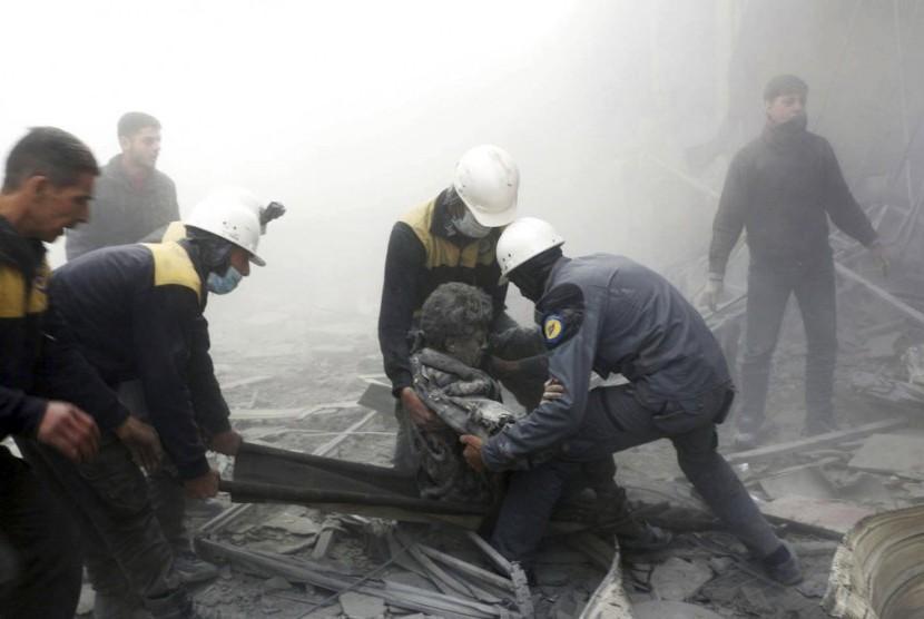 Petugas menolong seorang warga terluka setelah serangan udara menghantam Damaskus, Suriah.
