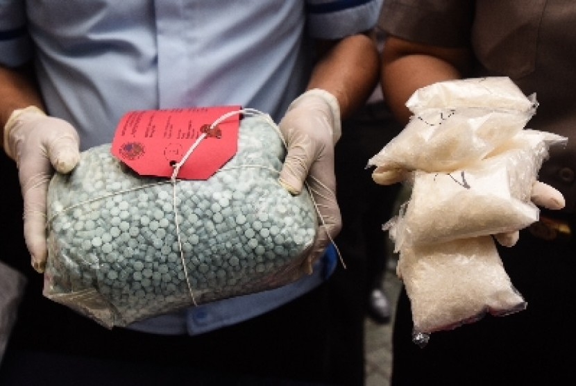 Petugas menunjukan barang bukti berupa pil ekstasi dan sabu.