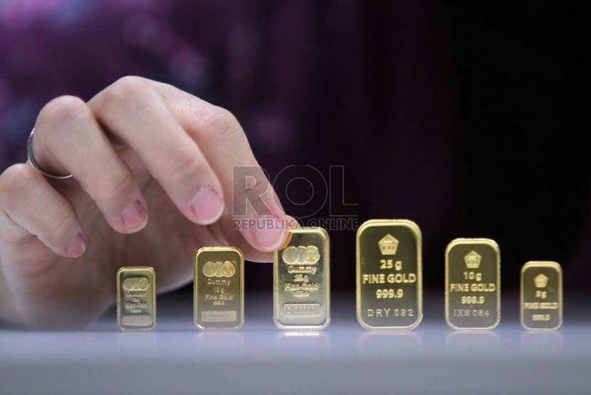 Petugas menunjukan contoh emas batangan atau logam mulia produksi Aneka Tambang di Pegadaian, Jakarta, Jumat (20/6).