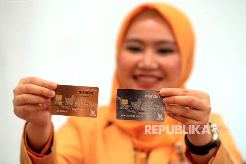 Petugas menunjukan kartu Mandiri Debit berlogo Gerbang Pembayaran Nasional (GPN) di kantor layanan Bank Mandiri, Jakarta, Senin (9/4). Bank Mandiri memperkenalkan kartu Mandiri Debit berlogo GPN untuk meningkatkan efisiensi dan menekan biaya transaksi antarbank.