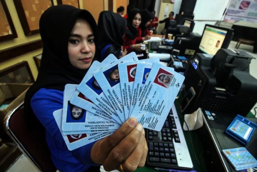 Petugas menunjukkan Kartu Tanda Penduduk elektronik (e-KTP).