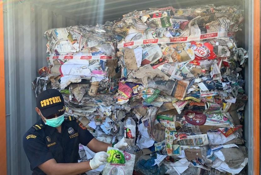Petugas menunjukkan kontainer yang berisi sampah kertas impor Australia yang bercampur dengan sampah rumah tangga. Delapan kontainer berisi sampah dari Australia akan dipulangkan oleh Bea Cukai Tanjung Perak.