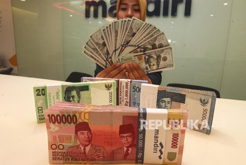 Petugas menunjukkan pecahan mata uang dolar AS dan rupiah di Plaza Mandiri, Jakarta. ilustrasi