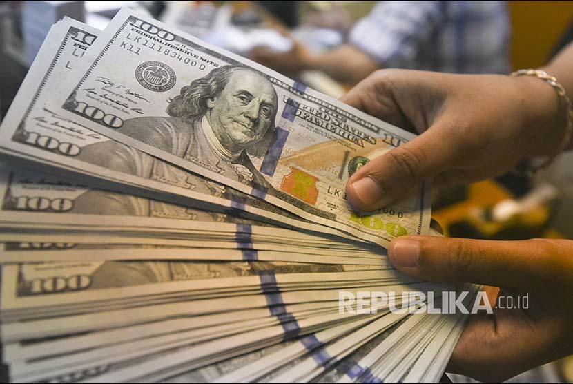 Petugas menunjukkan uang dolar Amerika Serikat di gerai penukaran mata uang asing Ayu Masagung di Jakarta. (ilustrasi)