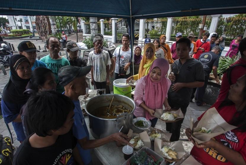 Petugas menyiapkan nasi dan lauk yang akan dibagikan gratis kepada kaum dhuafa dan fakir miskin(Ilustrasi).