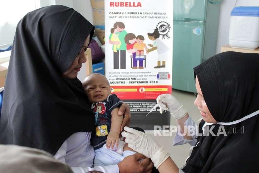 Petugas menyuntikan Vaksin Campak dan Rubella (MR) kepada bayi saat dilakukan imunisasi di Puskesmas Darussalam, Banda Aceh, Rabu (19/9).