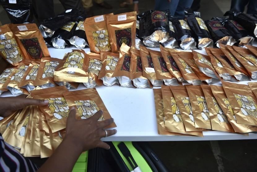 Petugas merapikan barang bukti tembakau gorila.