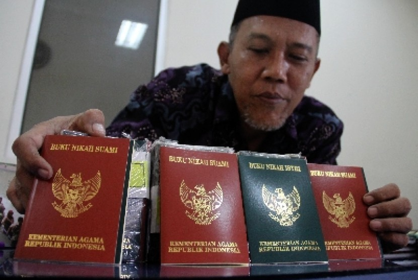 Petugas merapikan buku nikah di Kantor Urusan Agama (KUA) di Jakarta Pusat.